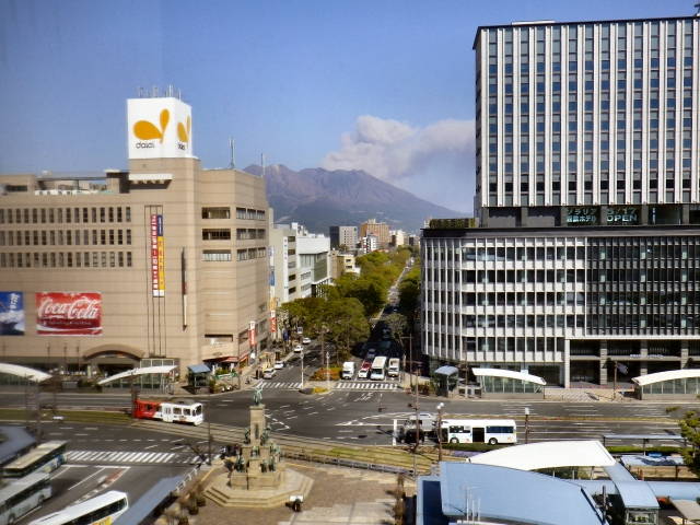 Sakurajima showering the city with ash, as viewed from Kagoshima-chuo Station